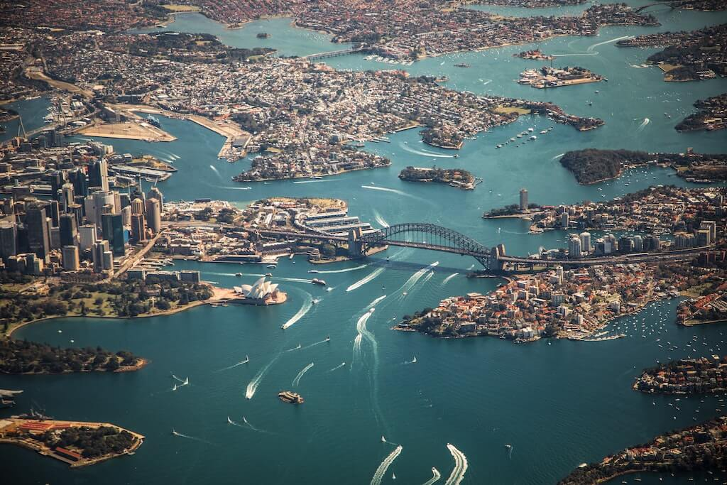 A bird's eye view of Sydney, with landmarks such as the Opera House and the Harbour Bridge