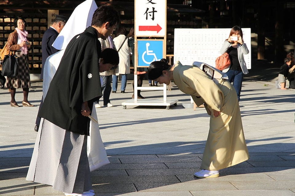 japanese girl bowing to friends