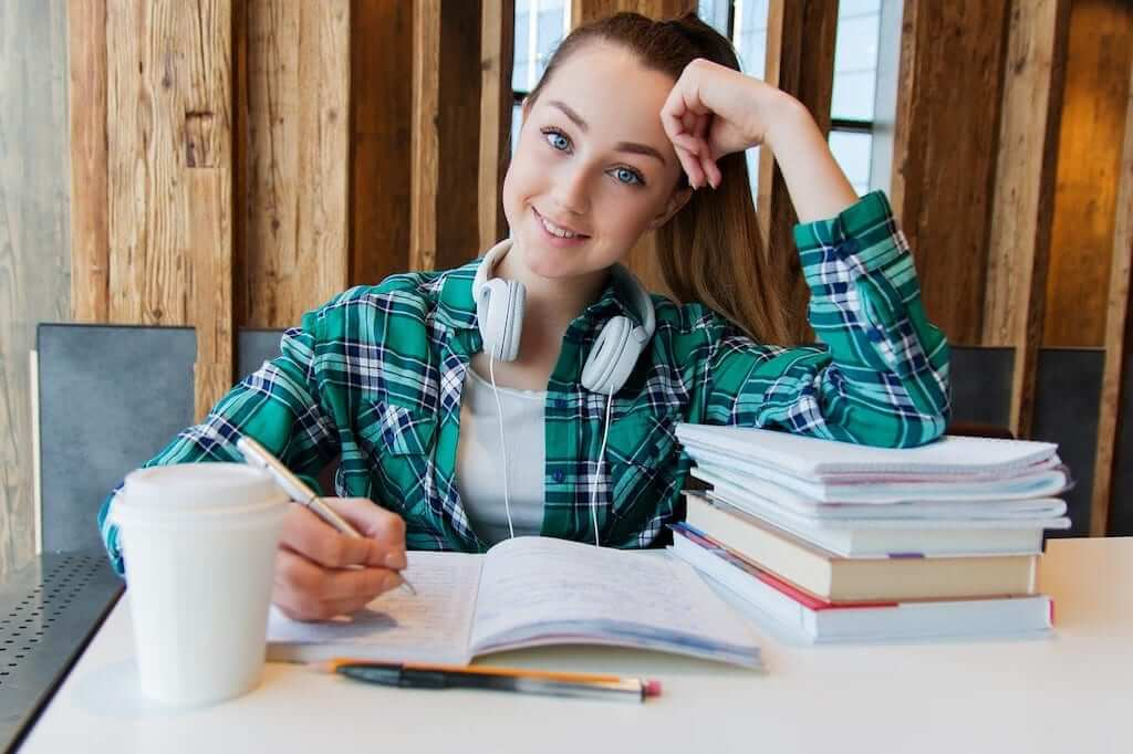 girl smiling while studying french with books