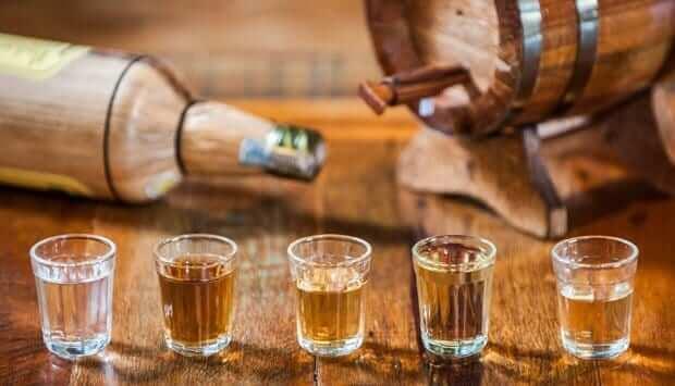 Pouring Cachaça into small glasses