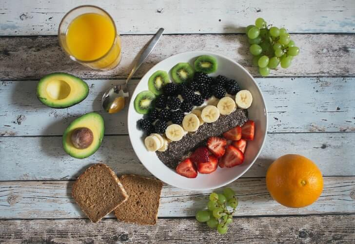 A bowl of acai with fruits, avocado and a glass of juice