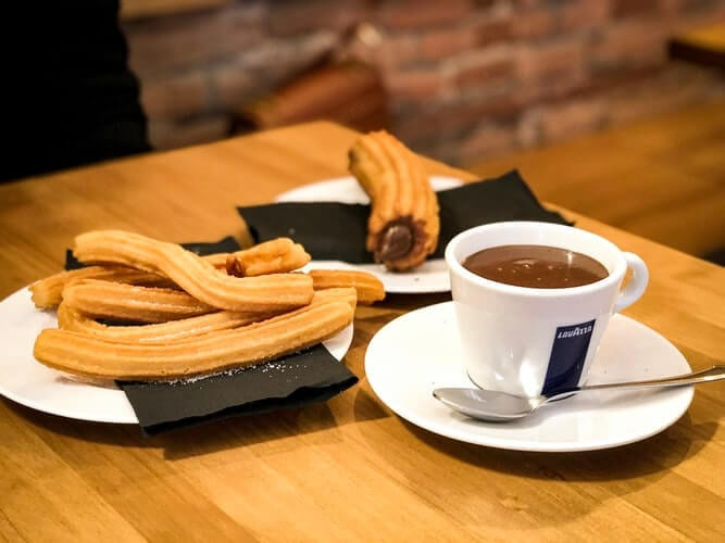 Churros and chocolate on a table