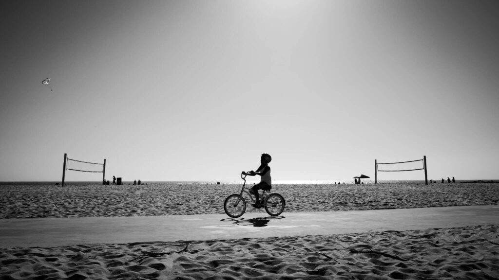 Black and white photo of a boy cycling along the beach