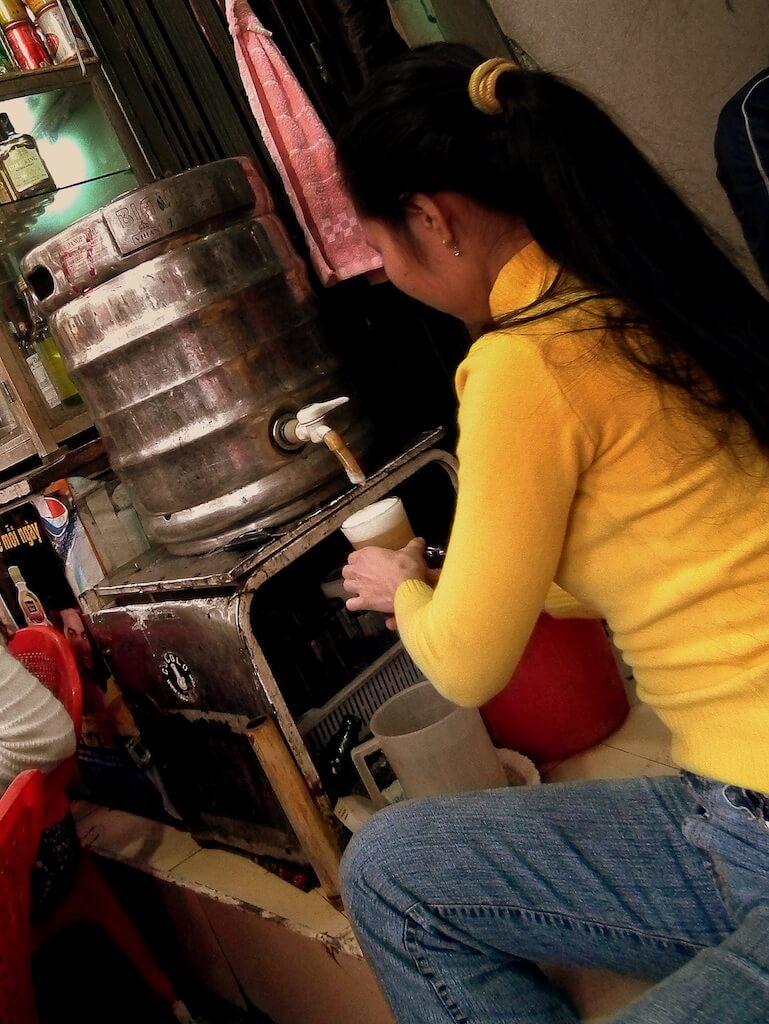 Woman pouring fresh Hanoi beer