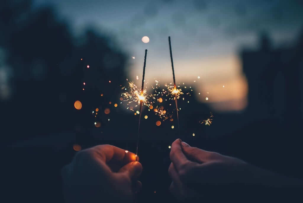 Hands holding small firecrackers in the dark