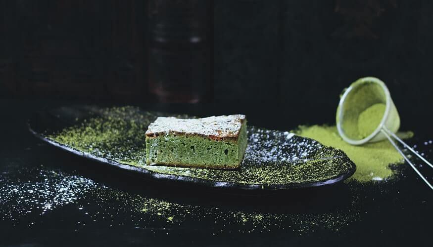 Matcha cake on a plate and matcha powder