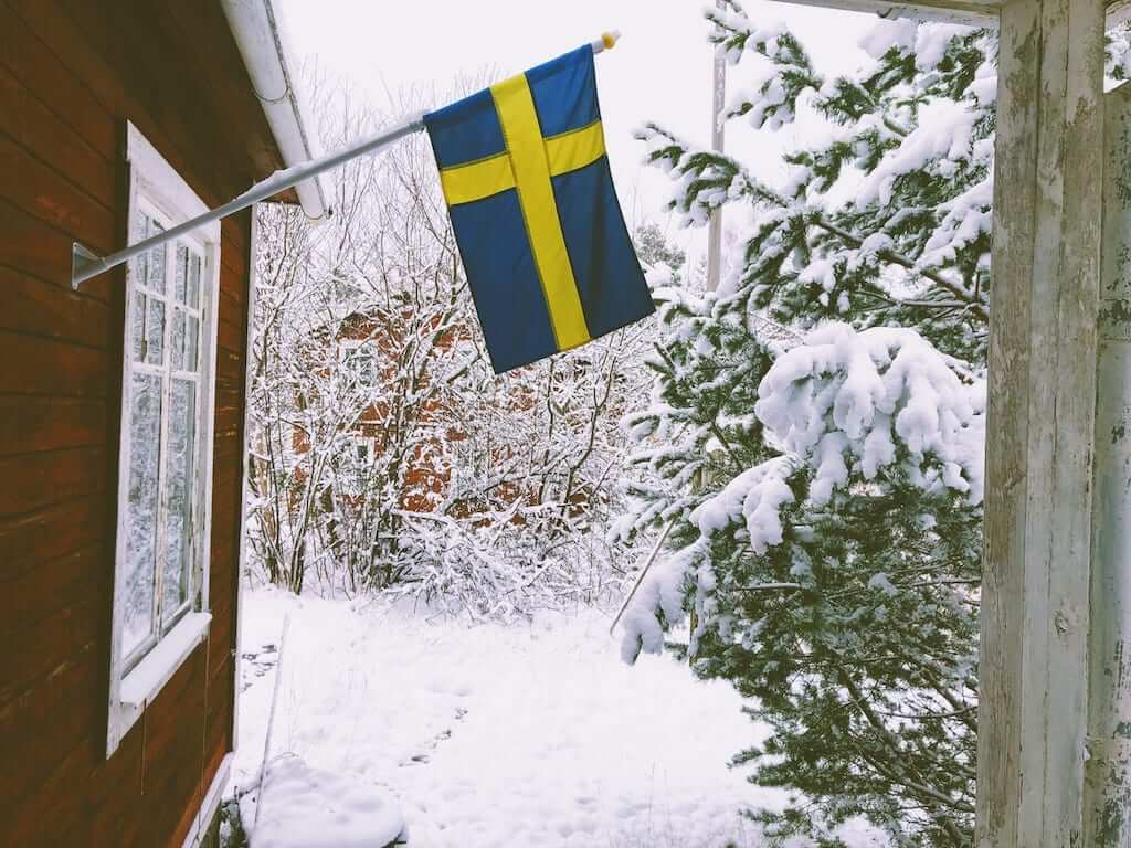 Swedish flag hanging outside a house in winter