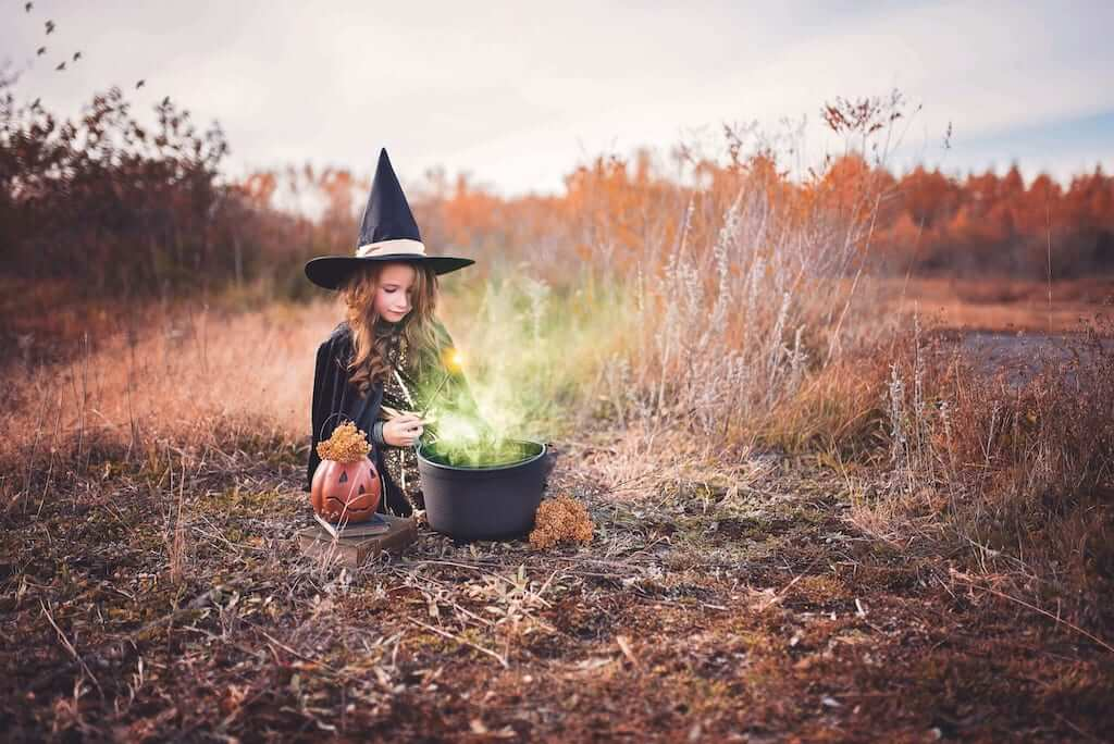 Girl dressed in witch clothing and brewing spells