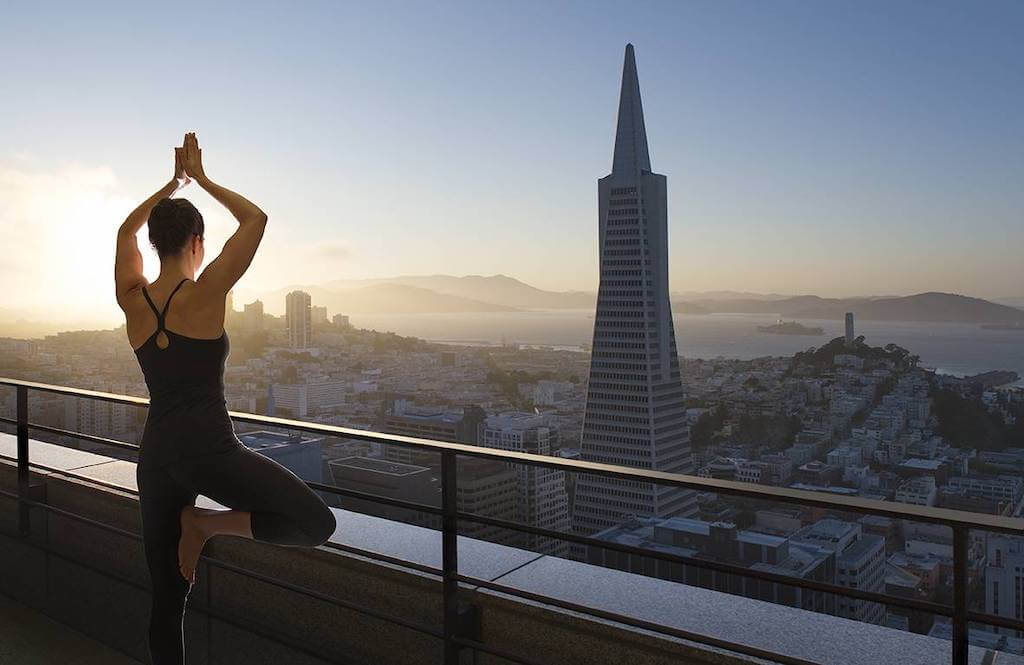 Woman doing yoga from her balcony
