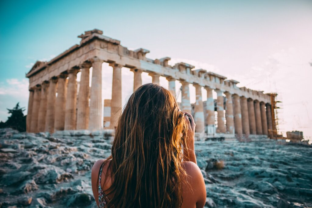 woman photographing the parthenon in athens - apps to learn greek