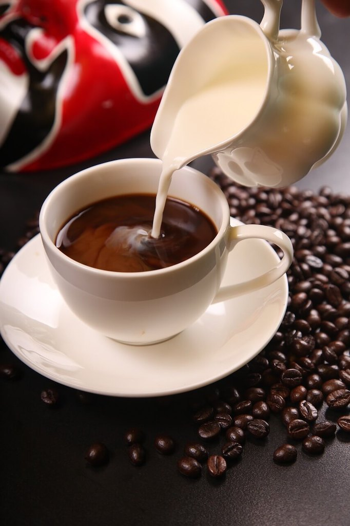 pouring milk over a cup of coffee with beans surrounding it