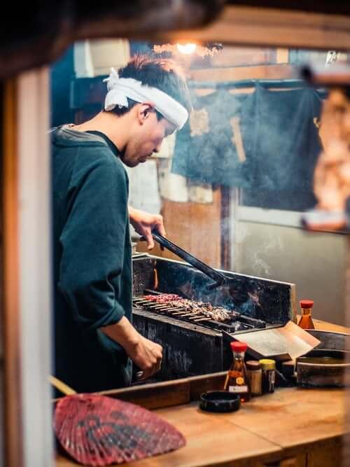 man grilling meat in japan