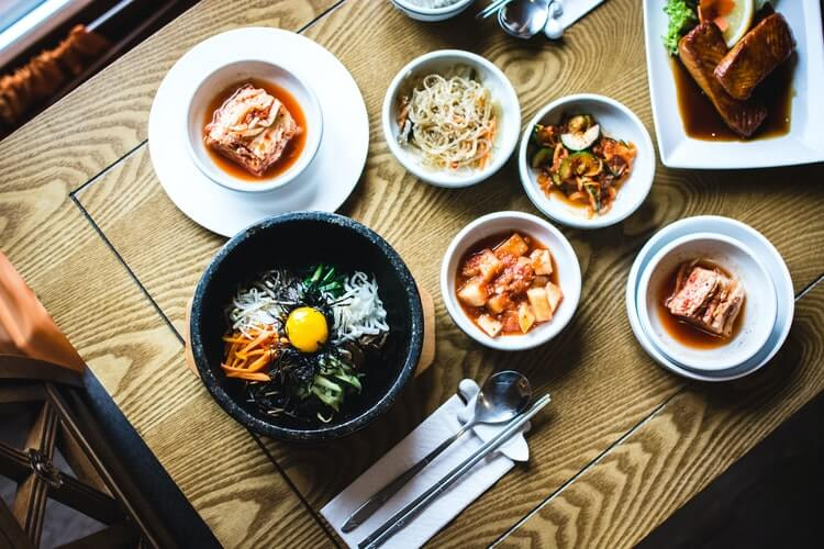 A korean meal with bibimbap, kimchi and side dishes
