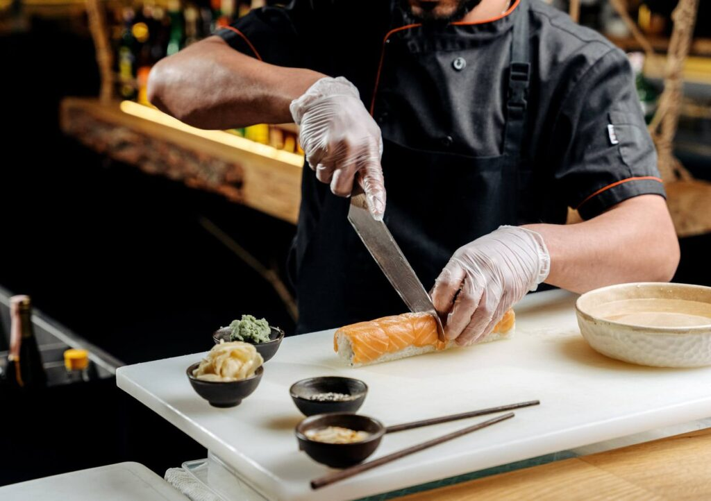 chef cutting sushi with a knife