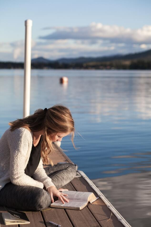 girl studying latin by the lake