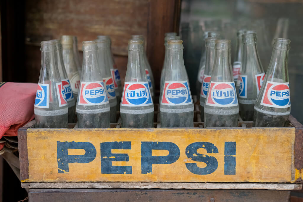 Old fashioned Pepsi bottles sitting in a wooden crate.